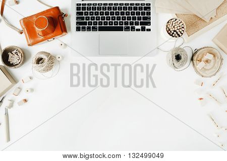 freelancer retro brown style workspace with laptop vintage photo camera craft envelope tools and twine on white background.