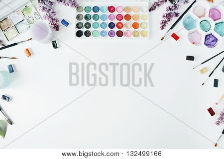 Watercolor and brushes at white background. Flat lay top view