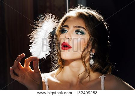 Young fashionable woman with bright makeup and red lips on pretty sexy face holding feather on dark background closeup