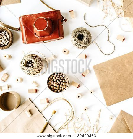 flay lay composition for bloggers artists magazines and social media. freelancer retro brown style workspace with vintage photo camera craft envelope pencils tools and twine on white background.