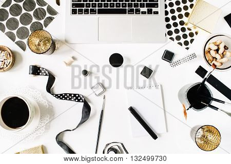 flay lay composition for bloggers artists magazines and social media. freelancer black style workspace with laptop black coffee sketchbook napkins ribbons paintbrushes on white background.