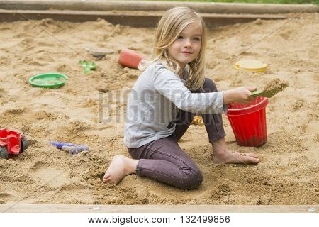 Happy little girl playing in a sandbox on the playground. Summertime children activities
