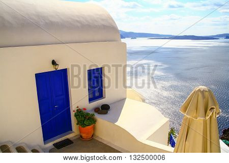 Whitewashed building wih blue door overlooking the Aegean Sea in Santorini Greece