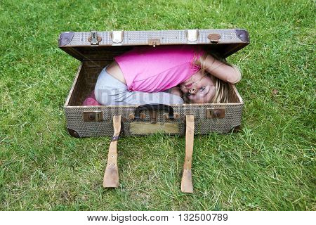 child blond girl inside a suitcase on green grass lawn