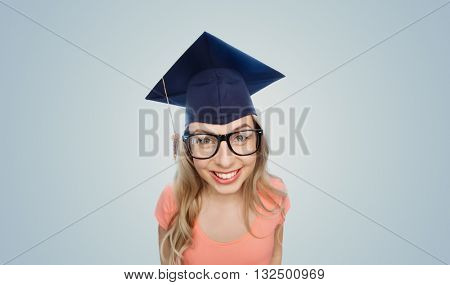 people, graduation and education concept - smiling young student woman in mortarboard and eyeglasses over gray background