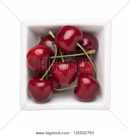 Cherries in a square bowl isolated on white background
