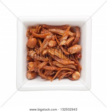 Fried anchovies and peanuts in a square bowl isolated on white background