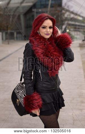 portrait of a girl with red hair, leather jacket, skirt, bag and cuffs and collar of red feathers in a urban scene