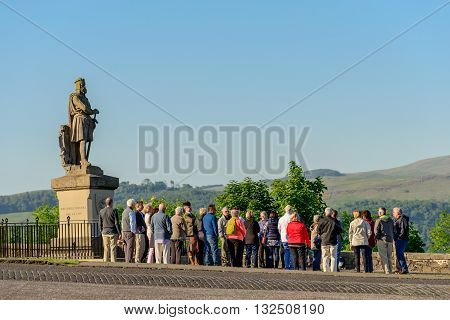 STIRLING SCOTLAND - JUNE 01 2016: A large group of tourists in front of the statue of King Robert the Bruce at Stirling Castle.