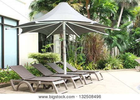 relaxing rattan chairs with a big umbrella beside the swimming pool