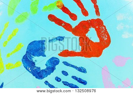 two hands imprint on the bright blue wall