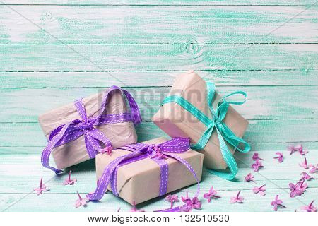 Festive gift boxes and lilac flowers on turquoise wooden background. Selective focus. Place for text.