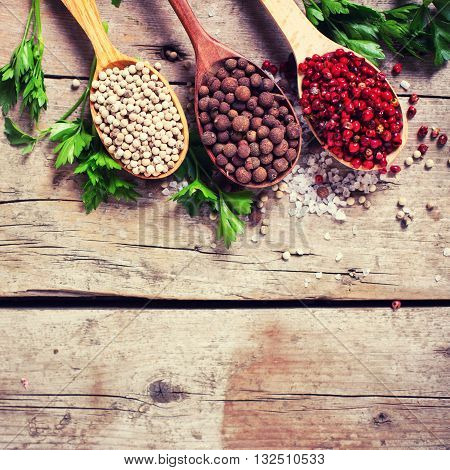 Seasoning for cooking. Red white and allspice pepper in wooden spoons on aged wooden background. Selective focus. Flat lay. Top view. Place for text. Toned image.