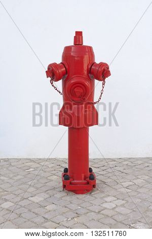 A red metallic fire hydrant in the ground for fighting urban fires