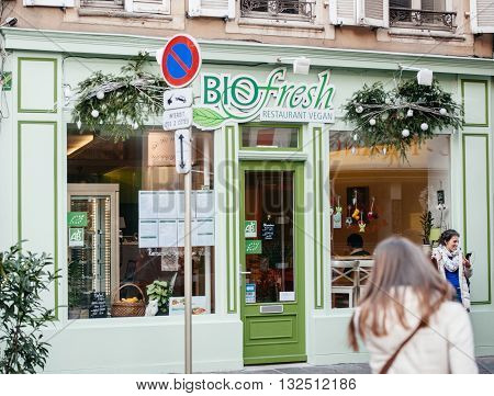 MULHOUSE FRANCE - DEc 19 2015: BIO Fresh Vegan restaurant facade painted in green colod with happy cystomer talking on the phone outside