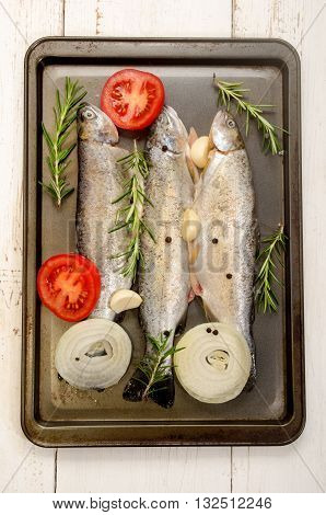 three fresh trout in a roasting tin with tomato slice garlic pepper corn coarse salt and rosemary