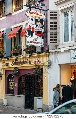 MULHOUSE FRANCE - DEC 19 2015: Alsacian Restaurant restaurant facade painted in yellow and Pig Logo on the streetof Mulhouse France