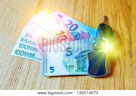 car keys lay on euro banknotes and wooden table
