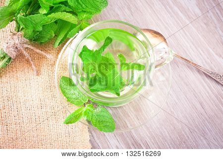 Tea with fresh mint leaves in a transparent cup on the table top view
