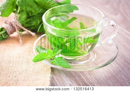 Cup of mint tea and a bunch of mint on the table