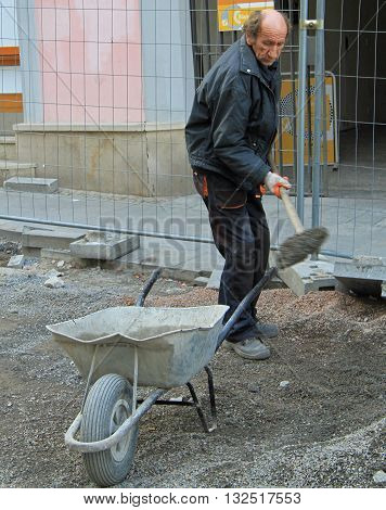 Man Is Carrying Wheelbarrow With Cement