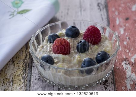Homemade bircher muesli with summer fruits in glass dish with napkin on wooden background