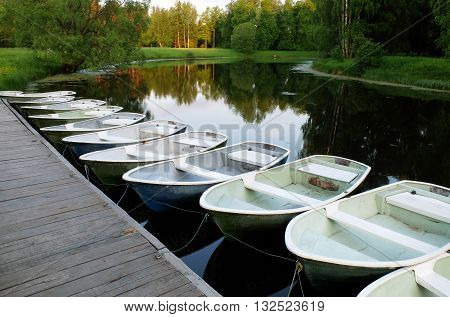 Saint Petersburg, Russia, may 18, 2016: boat wooden jetty with anchored rowing boats. Boats at the pier waiting for their captains. Park the boat on the water. A lot of boats on the shore.