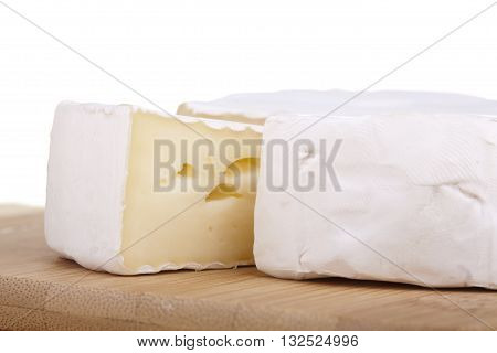 Closeup of tasty camembert cheese and salami sausage on bamboo background