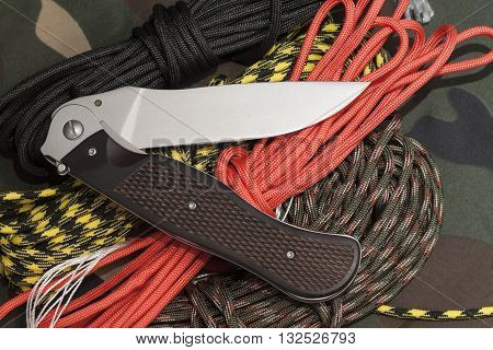 tactical folding knife with a rope on camouflage background