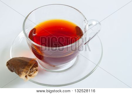A cup of tea with a used teabag on a white background
