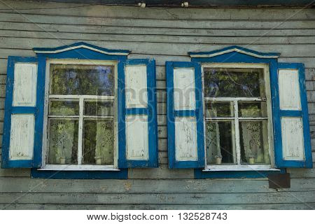Two windows with shutters and curtains on old wooden house. Country house.