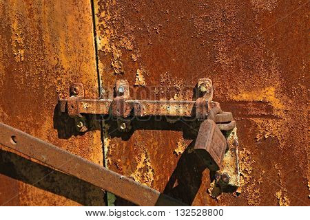 old rusty bolt with lock on the iron gate closed