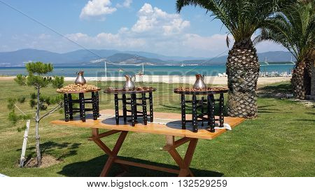 Three round tables with metal pitchers, cinnamon, walnuts stands on the grass. In the background, beach, sea and palm trees.