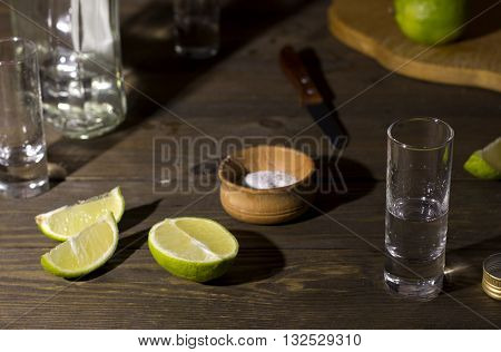glass with tequila on a wooden table green sliced lime knife