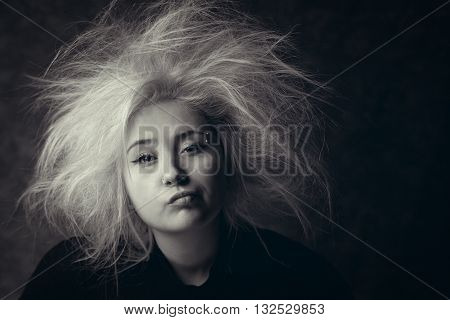Portrait of annoyed girl with wild hair, photo in black and white. Tired woman with boring face.