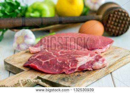 Beef vegetables and hammer for meat on a wooden table.