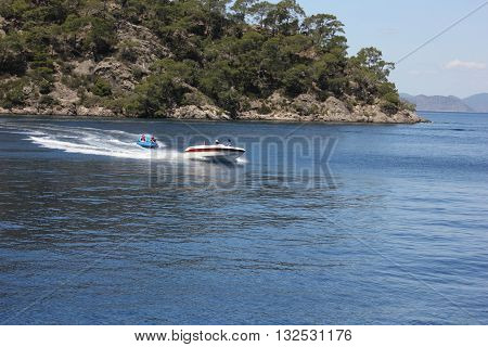 FETHIYE, TURKEY 26th MAY 2016: Tourists having fun riding in inflatables being pulled by a speedboat in a bay at Fethiye ,Turkey, 26th may 2016