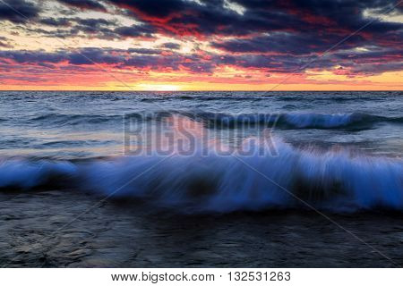 Sunset over Lake Michigan with gale winds create large waves crashing on to the beach.