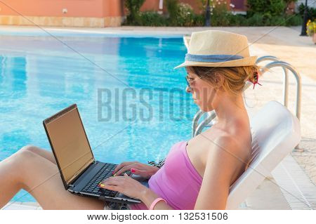 Young Woman Working On Laptop By The Pool