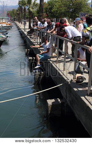 27TH MAY 2016, FETHIYE, TURKEY: Tourists watching Turkish men fishing along the promenade at fethiye in turkey, 27th may 2016