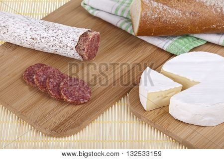 Tasty camembert cheese and salami sausage with bread on a wooden desk. Studio photo on white background