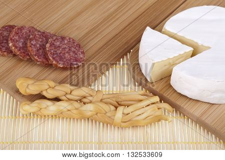 Tasty camembert cheese and salami sausage on a wooden desk. Studio photo on white background