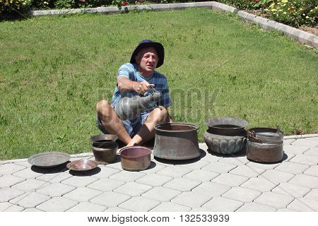 CALIS, TURKEY 28TH MAY 2016 : An Englishman with his purchase of old antique copper pots which he bought in Calis in Turkey, 28th may 2016