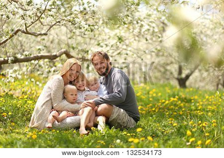 Happy Family Of Five Portrait In Spring Flower Meadow