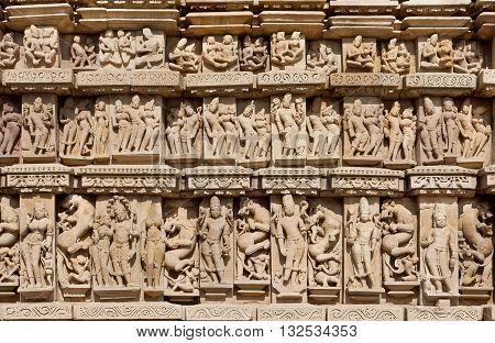 Sculptured background of historical indian temple of Khajuraho with Hindu gods and goddess. UNESCO Heritage site built between 950 and 1150 in India belong to Hinduism and Jainism.