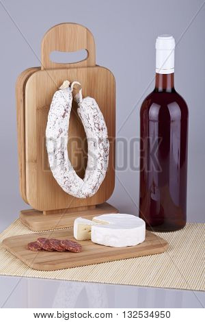 Tasty camembert cheese and salami sausage with a bottle of red wine. Studio photo.