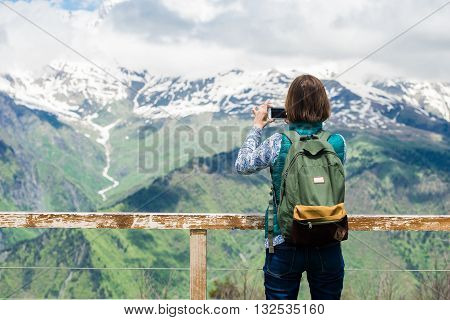 Pretty young woman girl stay on mountain top and taking picture with smart phone over beautiful background. Colorful photo of female tourist traveler