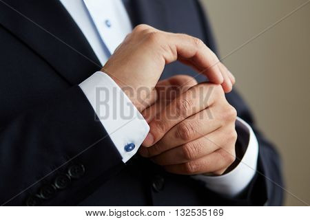 Man In Black Suit, Correcting The Sleeves Of His Shirt, Close Up