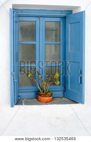 MELOS GREECE - SEPTEMBER 3 2012: Typical blue wooden window with shutters at an Aegean Islander whitewashed house.