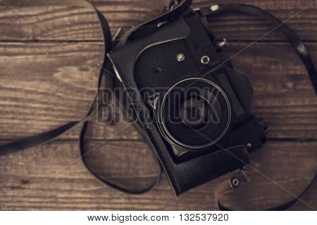 vintage analog camera on old rustic wooden background. top view